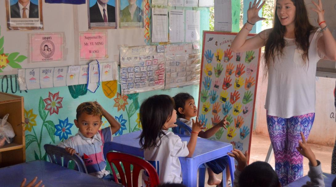 Projects Abroad Childcare volunteer helps children improve their English skills a a local community centre in Cambodia.